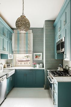 The robin's-egg blue cabinets in this room (designed by Sheila Bridges) are so striking that the rest of the decor simply has to fall in line.