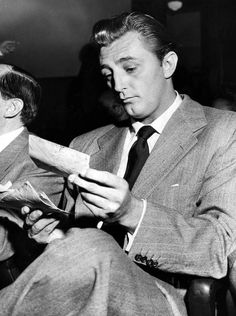 Robert Mitchum looks over fan-mail while waiting for the judge to arrive at court, during his trial for possession of illicit substance 1948.