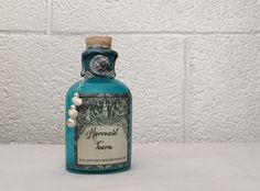 The perfect gift for the mermaid and magic lover in your life. The tears are turquoise that change to a light, iridescent aqua blue swirls when shaken, and settles back down to a clear turquoise in a few minutes. This enchanting bottle is finished with silver tone chain, shells and pearl beads, blue cord, an aged label, an aged cork, a faux wax seal and is sealed with marbled blue, white and black faux wax. This small but detailed bottle will add interest to your potion bottle collection…