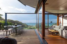 Wooden Framed Glass Sliding Exterior Door Between Fabric Padded Sofa And Outdoor Dining Sets In The Wooden Patio.