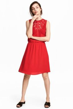 Short, sleeveless dress in a crêpe weave with lace at the top and a small opening with a button at the back of the neck. Seam at the waist with narrow elast