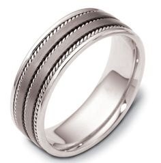 14 kt white gold and titanium , comfort fit, 7.0 mm wide wedding band. The ring has 3 handmade ropes inlayed in the ring. The two flat pieces in the center have a matte finish. The rest of the band has a polished finish. Different finishes may be selected or specified.