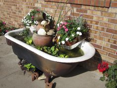 Playing in the tub    Claw foot cast iron tub from my childhood purchased at Dad and Moms farm sale. Water fountain and plants local garden store. Paint pans clamp perfectly to the side to hold plants.  Pitcher garage sale. Cattails from ditch. 3 fish from Kayla and BethAnn's big fishing trip to the pond.