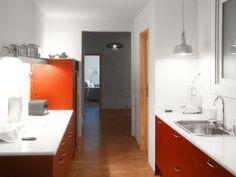 Vista de la cocina de mármol blanco y muebles rojos integrada en el pasillo de la casa. Diseño y reforma de 08023 Arquitectos - Barcelona
