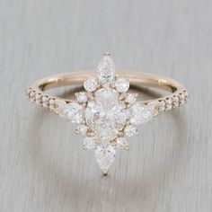 Rose gold vintage ballerina engagement ring. Marquise oval diamond with hidden peak stone, fishtail / scallop setting.