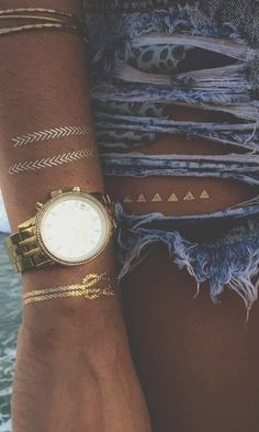 Loving this! The peek-a-boo metallic tattoo in the window of the cut out,, perfect.    Gold Jewels & Watch // Shredded Denim