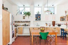 Cozinha tem piso de cimento queimado rosa, móveis feitos com compensado e bancada de alvenaria.
