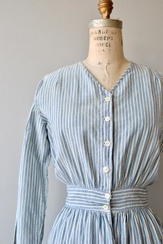 Vintage 1910s blue and white pinstripe cotton chore dress, mid length with fitted waist, oversized front pockets and white buttons. --- M E A S U R E M E N T S ---  fits like: small bust: 39 waist: 26-27 hip: free length: 47 brand/maker: n/a condition: very good, small hole in right arm,