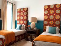 I love the color scheme and the use of the bold pattern on both the tailored bedskirt and the oversized upholstered headboard.