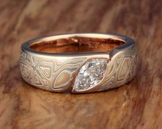 Mokume Wave Engagement Ring with Marquise Stone. This engagement ring consists of a band of mokume gane, contoured to a marquise-shaped stone. This snag-free ring widens towards the top, to allow for the gemstone to sit flush with the mokume.