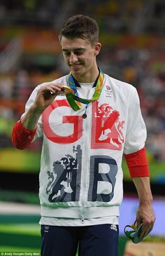 Great Britain gymnast Max Whitlock looks delightedly at the gold medal he just won, in the floor exercises, at Rio 2016