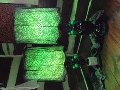 Green and black Halloween lamps.  - 2 thrift store lamps: $17 for both - 1 black lace Halloween table cloth from the dollar store: $3 - 2 bags of green glitter skull ornaments from the dollar store: 2x $1 - 1 can of black spray paint: $5 - 2 green decorative light bulbs from hardware store: $3  Total: $30 for two fun Halloween lamps!