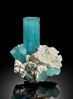 an aquamarine crystal with albite (a feldspar mineral that contains sodium)