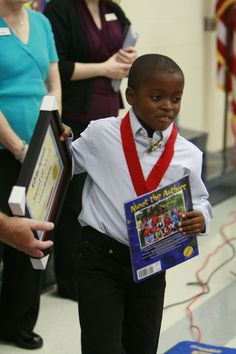 A young author receives his published book and a medal for helping write the national grand prize winning book in Scholastic's Kids Are Authors contest.