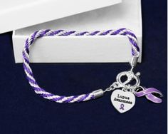 """Lupus Purple Ribbon Rope Bracelets. Each bracelet has two charms: a purple ribbon charm and a silver heart charm that says """"Lupus Awareness"""". The bracelets are approximately 8 inches. Packaged 18 bracelets per pack. Product Code: B-02-4LU"""
