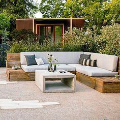 Sleek backyard garden with wood wrap-around seating and a concrete cube coffee table #modern #design #outdoor