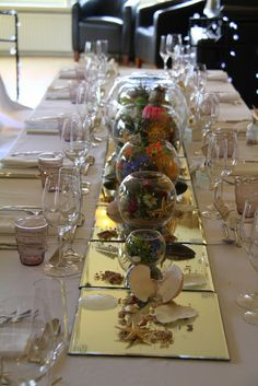 "The Wedding Breakfast was served in The Salon at The Grand, all of the guests were seated around one long table, we'd dressed the table with a series of varying sized Goldfish Bowls each filled with an ""Under the Sea Scene"""