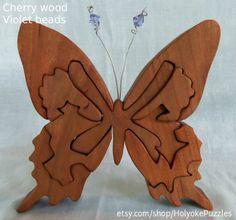 Deze handgemaakte vlinder jigsaw puzzel is gesneden uit hoogwaardige cherry en maatregelen 6 x 6 x ⅞ inch (15 x 15 x 2.2 cm). Het patroon is een origineel ontwerp door Barbara die u niet ergens anders vinden zult. Na zorgvuldige hand schuren, verzegeld we deze puzzel hardhout met een niet-toxisch Tung olie afwerking uit de fijne cherry korrel te brengen. Crystal-bedekte antenne eigenzinnigheid en magie aan de mooie vlinder toevoegen. Beschikbaar met beide bleke violet of iriserende parels…