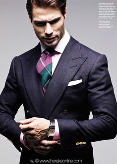 Navy double-breasted silk blazer with gold buttons, fuchsia and green wool and silk tartan tie, both Tom Ford. Santos 100 Chronograph timepiece with navy leather strap, and Santos de Cartier black lacquer and sterling silver cufflinks, both Cartier. Silver bracelet, Hermes. Pink cotton made to measure shirt, by Charvet