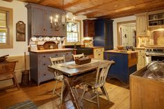 A rustic country kitchen with distressed table, chairs, and cabinetry in a variety of muted colors including gray and cream. The small butcher-block topped island and cabinet in the back left corner are painted a distressed deep royal blue that pops against the light pine flooring. Accents in this home include an antique butter churn and table that displays a carved wooden bowl and spoon. As a centerpiece on the small table, an antique tool box holds the checkered fabric napkins.