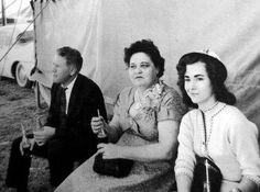 ELVIS PRESLEY - Homecoming Concert at the Tupelo Fairgrounds in Mississippi on Wednesday, September 26, 1956 - matinee performance. Vernon and Gladys Presley are pictured with Elvis's Memphis girlfriend, Barbara Hearn. Though it was late fall, the temperature had risen to such a ghastly degree that they melted in their folding chairs. Gladys Presley sweltering in a brocade dress and stockings, a locket with a picture of Elvis around her neck.