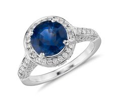 This gemstone and diamond ring showcases a vibrant round blue sapphire accented with a halo of sparkling round diamonds.