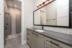 With an expansive mirror and vanity, tons of cabinets for storage and a large standing shower, the secondary bathrooms are nearly as luxurious as the master! Custom Home Designs, Custom Home Builders, Custom Homes, Standing Shower, Japanese Minimalism, Design Firms, House Plans, House Design, Modern Homes