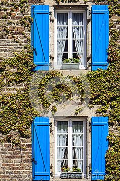 A typical French facade with windows and blue shutters in Brittany, France.