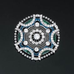 A Belle Epoque Diamond, Sapphire and Emerald Brooch   Of pierced openwork design, the central diamond-set cluster within a pierced metalwork surround and six further diamond collet accents, with calibr-cut sapphire and emerald outer edge within a scalloped and knife-edge old-cut diamond collet frame, circa 1895, 3.60 cm wide