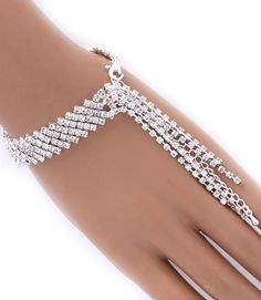"""This fashion bracelet features a prong set, tassels over your finger and a lobster clasp all adorned with crystal studs. The tassels are 2 3/4"""" long and textured. The bracelet is metal casting. Size: 8"""" Long 
