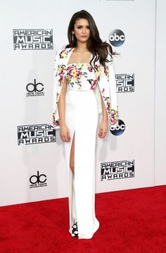 Nina Dobrev wears an embroidered crop top, fitted jacket, white skirt with high slit, and printed heels