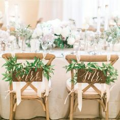 Bride and Groom chairs decorated with eucalyptus and signs