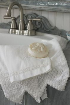 Full of things to love: old fashioned white sink with pewter-coloured taps; gorgeous antique linen towels trimmed with lace; fragrant carved soap...