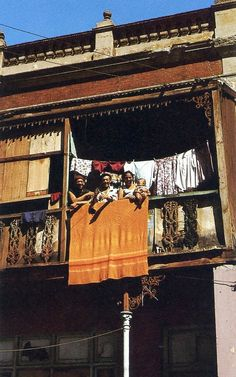 Colourful washing and people on a balcony in District Six