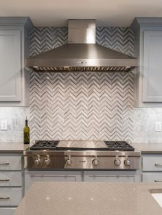 Gray Transitional Kitchen With Herringbone Backsplash Behind the Wolf cooktop (calling all chefs! Behind Stove Backsplash, Gray Subway Tile Backsplash, Herringbone Backsplash, Kitchen Backsplash, Stone Backsplash, Grey Kitchen Island, Grey Cabinets, Transitional Kitchen, Kitchen Remodel