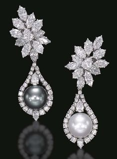A PAIR OF DIAMOND AND CULTURED PEARL EAR PENDANTS, BY HARRY WINSTON. Each detachable white or black cultured pearl pendant, measuring approximately 12.10 mm, within a circular-cut diamond drop-shaped surround, accented by pear-shaped diamonds, suspended by a pear and marquise-cut diamond cluster, mounted in platinum. Signed Winston for Harry Winston.