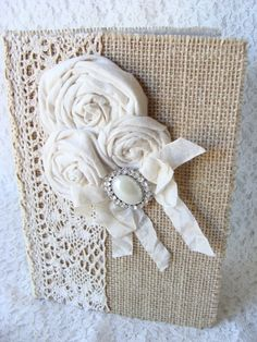 Shabby rustic chic hardback book covered in burlap and different lace trims, three handmade fabric rolled roses with a pretty rhinestone and pearl