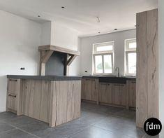 De landelijke keuken van rustiek eiken in white wash wordt prachtig afgemaakt met zwart granieten aanrechtblad dat is gefrijnd. De keuken is geheel op maat gemaakt.