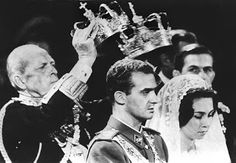 King Paul of Greece performs the Greek Orthodox tradition of holding crowns over the heads of his daughter, Princess Sophia, and her husband, Prince Juan Carlos of Spain, during their wedding ceremony on May 14, 1962.