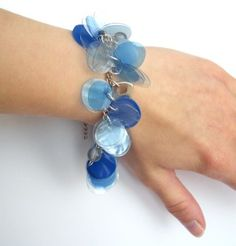Upcycled jewelry blue charm bracelet made of recycled plastic. Punched from various colors of plastic bottles. No real instructions given.