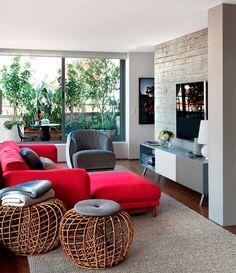 Usar um sofá escarlate é uma decisão ousada, porém o modelo Rest (Micasa) caiu muito bem entre peças mais neutras. Da mesma loja vem a poltrona matelassada Redondo, de Patricia Urquiola. Projeto SAO Arquitetura