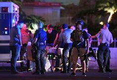 LAS VEGAS, NV - OCTOBER 02:  Police officers stand by as medical personnel tend to a person on Tropicana Ave. near Las Vegas Boulevard after a mass shooting at a country music festival nearby on October 2, 2017 in Las Vegas, Nevada .A gunman has opened fire on a music festival in Las Vegas, leaving over 20 people dead. Police have confirmed that one suspect has been shot. The investigation is ongoing.  (Photo by Ethan Miller/Getty Images)
