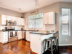 Traditional Kitchen with Flush, Limestone Tile, Raised panel, Hampton Bay Cabinets in Satin White, Hardwood floors, U-shaped