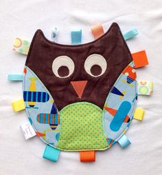 Owl Tag Toy for a baby boy with orange and blue appliquéd features and ribbon tags backed with flannel on Etsy, Sewing With Nancy, Sewing For Kids, Baby Sewing, How To Sew Baby Blanket, Lovey Blanket, Baby Boy Toys, Baby Kids, Sewing Crafts, Sewing Projects