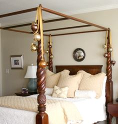 Canopy bed with oversized ornaments hung with gold ribbon