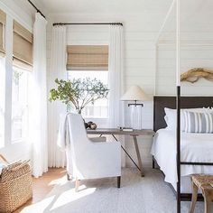 coastal bedroom decor with modern four poster bed with farmhouse bedding, farmhouse bedroom with shiplap and driftwood wall art, coastal master bedroom with woven shades, neutral airy bedroom decor with desk in bedroom, small home office in bedroom Farmhouse Master Bedroom, Modern Bedroom, Contemporary Bedroom, Master Bedrooms, Trendy Bedroom, Natural Bedroom, White Bedrooms, Minimalist Bedroom, Contemporary Landscape