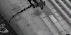 This aerial black-and-white video image shot with an infrared camera and made available by the Italian Coastguard Tuesday Jan. 17, 2012 appears to show passengers of shipwrecked cruise liner Costa Concordia slipping down the belly of the luxury liner one-by-one using a rope to reach a lifeboat, bottom left, late Friday