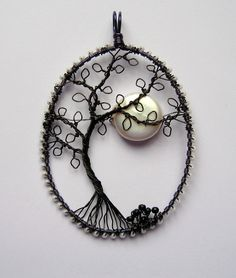 Craft wire, seed beads, and a freshwater coin pearl.  The frame is actually midnight blue wire, wrapped with pearlescent seed beads to represent stars.  The tree is black wire.