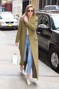 Gigi Hadid in a trench coat and slip ons and keeps it simple but bold all at once.