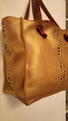 Gorgeous Personalized Gold Leather Shoulder Bag with Monogram  Spacious, sophisticated and chic, this gorgeous gold tote leather embellished with studs, is a must-have leather bag. With the monogram you can make this beautiful designer bag into your own one of a kind bag.  It is roomy, functional and versatile, with two handles to carry over your shoulder.  You can use it everywhere every day and for any occasion, and it will add charm, elegance and sophistication to your appearance.  This…